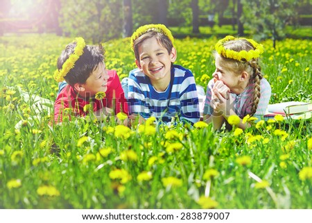 Happy children with dandelion wreaths relaxing on lawn in park  - stock photo