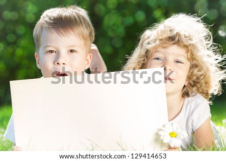 Happy children with paper blank and flower lying on green grass in spring park. Environmental conservation concept - stock photo