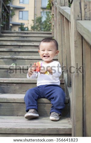 Happy Chinese baby boy playing a toy on stairs - stock photo