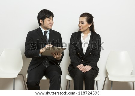Happy Chinese business man interviewing female applicant. - stock photo