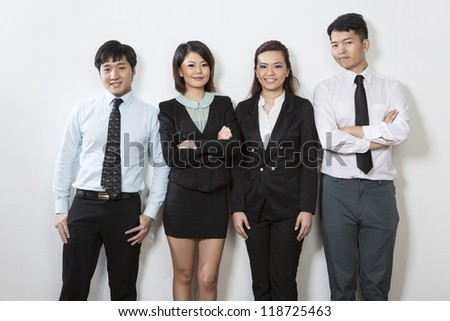 Happy Chinese business team standing in a row and leaning against a wall. - stock photo