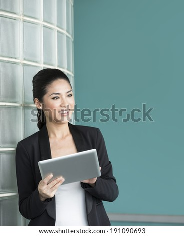 Happy Chinese business woman holding a tablet computer in office. Business woman Looking away thoughtfully. - stock photo