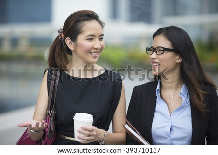 Happy Chinese Business women walking outside office & talking to each other. - stock photo