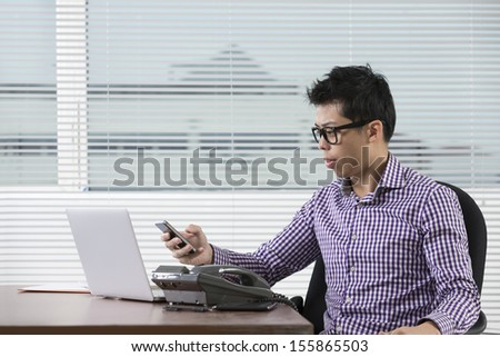 Happy Chinese businessman reading his smartphone in his office. Asian business executive at work. - stock photo