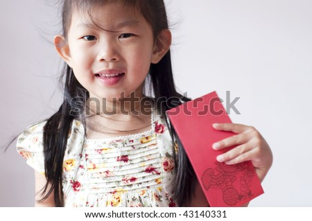 Happy chinese girl holding a chinese red envelope. Red envelope or red packet is a monetary gift which is given during holidays or special occasions, such as weddings or Lunar New Year. - stock photo
