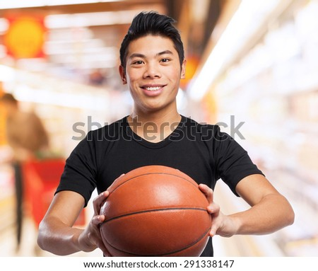 happy chinese sport man with basket ball - stock photo