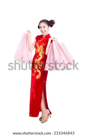 happy Chinese woman dress traditional cheongsam at New Year with shopping bag - stock photo