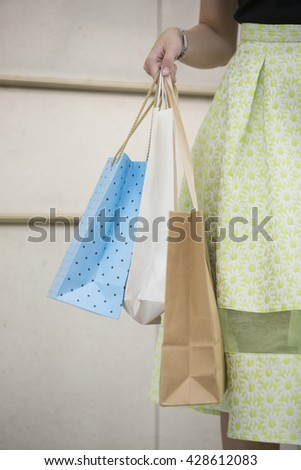 Happy Chinese woman walking on an urban street, holding shopping bags.  - stock photo