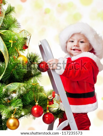 Happy Christmas baby standing on a step ladder decorating Xmas tree - stock photo