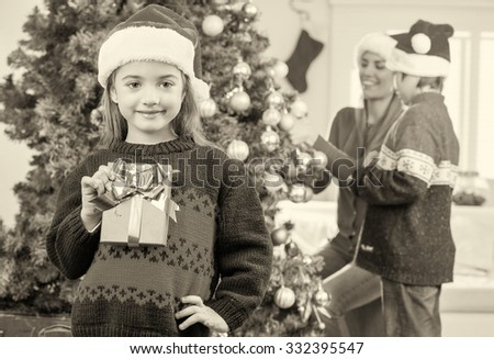 Happy Christmas family scene. Baby girl showing gift with her mother and brother decorating tree in background. - stock photo