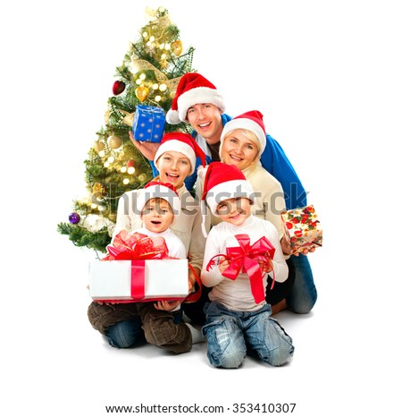 Happy Christmas Family with Gifts isolated on white, Decorated Christmas tree. Smiling Father, Mother and Children holding gift box. Smiling Dad, Mom and kids celebrating New Year, wearing Santa Hats - stock photo