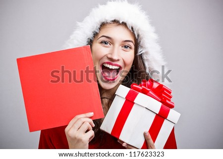 Happy Christmas girl holding a gift and a red board ready for your text - stock photo
