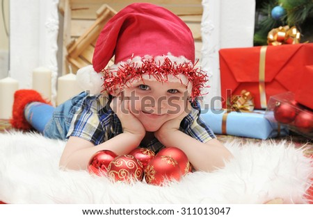 Happy Christmas. Happy boy with gifts by the fireplace. - stock photo