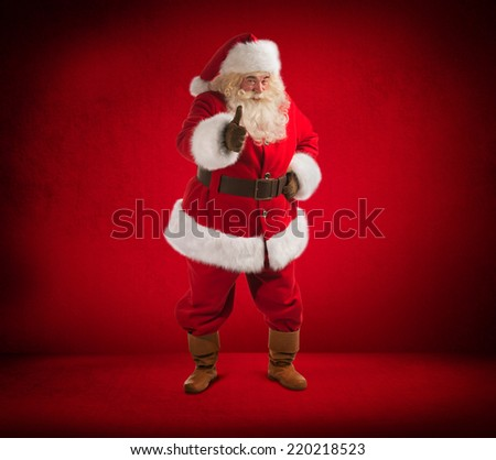 Happy Christmas Santa Claus showing thumb up. Red background. Full length - stock photo