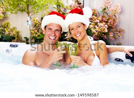 Happy christmas santa couple in hot tub. Vacation. - stock photo