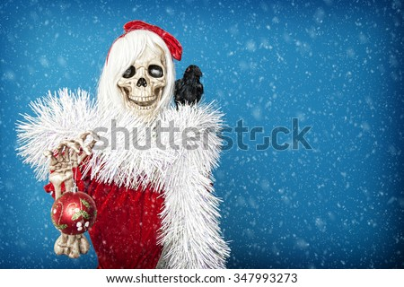 Happy Christmas skeleton holding a Christmas ball in snowy twilight. - stock photo