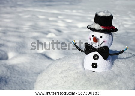 Happy Christmas snow man sitting in a snowy hill outdoors winter background - stock photo