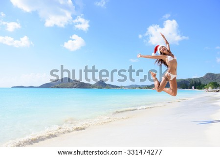 Happy Christmas vacation - girl jumping of joy and surprise on perfect white sand beach for winter holidays. Young woman wearing santa hat arms raised of happiness during vacations. - stock photo