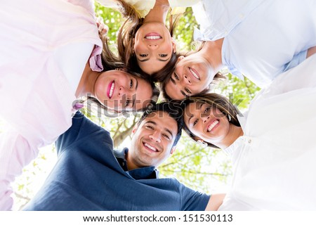 Happy circle of friends hugging together at the park - stock photo