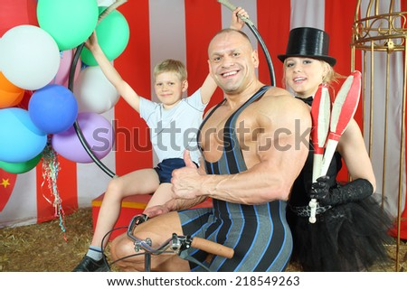 Happy  circus strong man, woman in cylinder and boy with retro bike with balloons in striped tent - stock photo