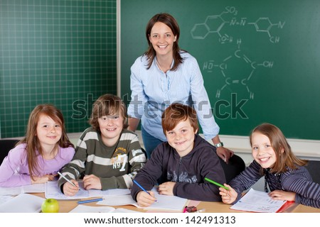 Happy class of young pupils with their young female teacher working together in a classroom sharing a desk - stock photo