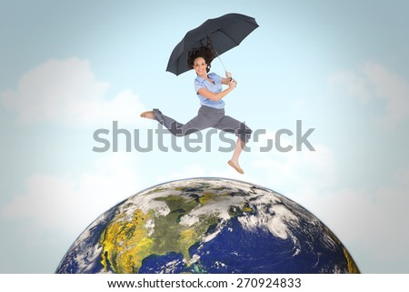 Happy classy businesswoman jumping while holding umbrella against blue sky - stock photo