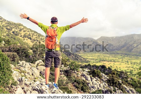 Happy climber hiker winning reaching life goal, success man at summit, successful business concept. Young runner hiker arms up outstretched,freedom and happiness rock climbing achievement in mountains - stock photo
