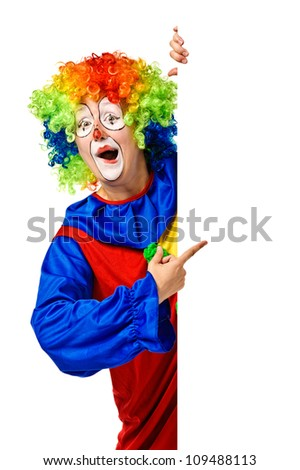 Happy clown holding the blank board and pointing. Isolated - stock photo