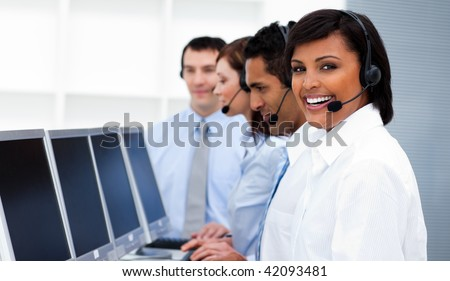 Happy co-workers with headsets on working in call center. Business concept. - stock photo