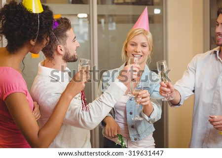 Happy colleagues toasting champagne in birthday party at creative office - stock photo