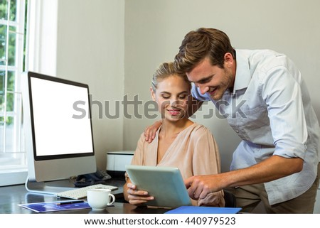 Happy colleagues using digital tablet at desk in office - stock photo