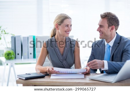 Happy colleagues working together on laptop and folder in the office - stock photo