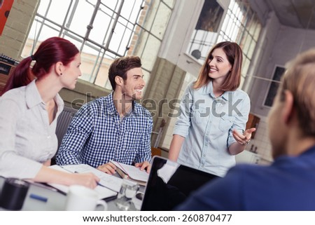 Happy College Friends Talking at the Office About their Project - stock photo