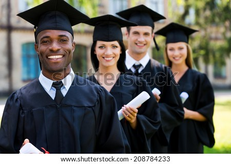 Happy college graduates. Four college graduates standing in a row and smiling - stock photo
