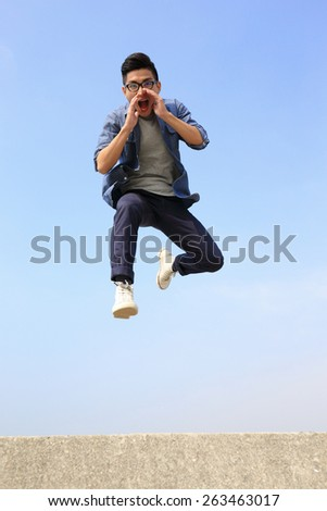 Happy College student man run and jump with blue sky background, full length, asian male - stock photo