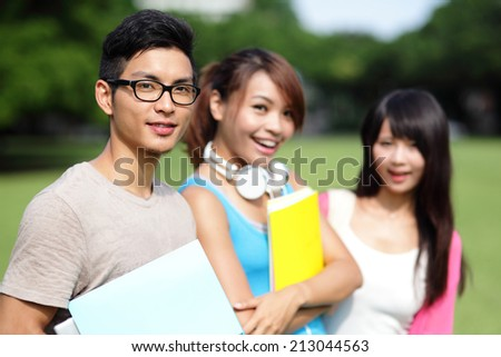 Happy College student man smile to you on campus lawn, asian - stock photo