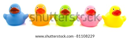 Happy colorful rubber ducks in a row isolated over white - stock photo