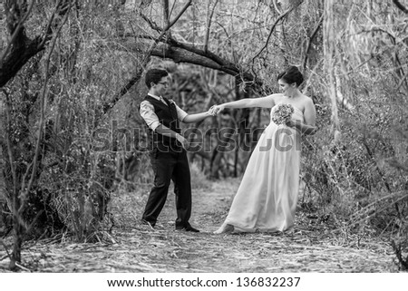 Happy committed couple dancing in the forest together - stock photo