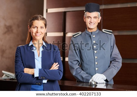 Happy concierge and smiling receptionist in a hotel as team in uniform - stock photo