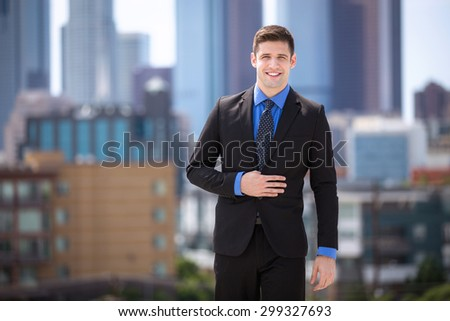 Happy confident attractive businessman in a suit downtown skyline rooftop - stock photo