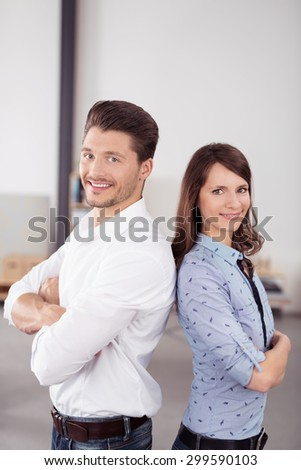 Happy Confident Business Couple in Back to Back, Smiling at the Camera While Standing Inside the Office. - stock photo