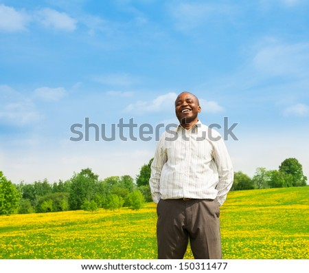 Happy confident laughing black man wearing shirt standing outside in the park on the yellow dandelion field - stock photo
