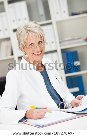 Happy confident senior businesswoman sitting working on paperwork at her desk in the office - stock photo