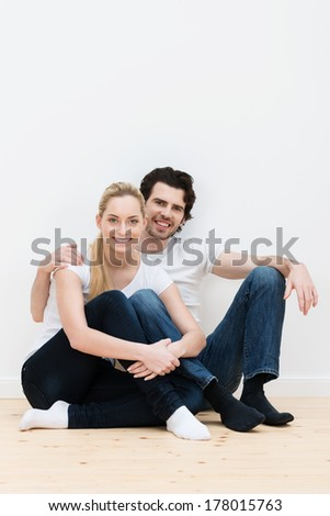 Happy contented couple in their new home sitting on the bare wooden floor in their socks smiling in an affectionate embrace, with copyspace on the wall above - stock photo