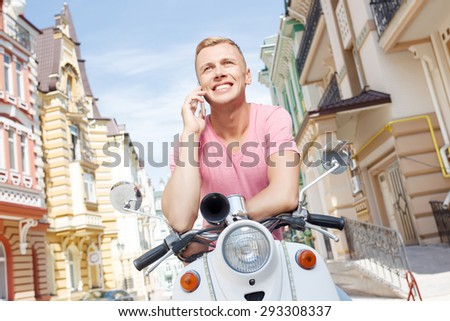 Happy conversation. Pleasant smiling man sitting on retro scooter and talking per mobile phone. - stock photo