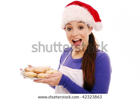 Happy cook holding plate of mince pies - stock photo
