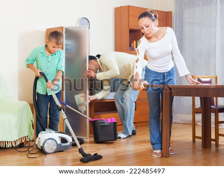 Happy couple and teenager boy cleaning with vacuum cleaner in living room - stock photo