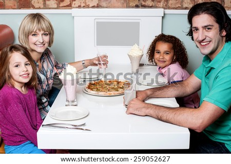 Happy couple and their children sitting in restaurant - stock photo
