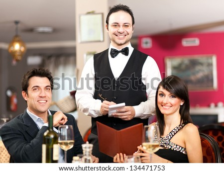 Happy couple and waiter smiling in the restaurant - stock photo
