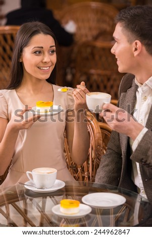 Happy couple are enjoying some cake and coffee at the coffee shop. - stock photo